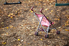 Dolls pram on empty playground stock image