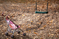 Dolls pram on empty playground Stock Photography