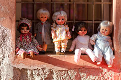 Dolls resting on a window Royalty Free Stock Image