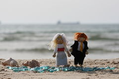 Dolls on sandy beach Stock Images