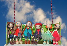 Dolls, toys ride on a swing Royalty Free Stock Images