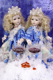 Dolls twins. Near the snow glasses of wine and red hearts. Royalty Free Stock Photos