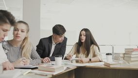 Dolly beweging van Studenten die voor onderzoek voorbereidingen treffen terwijl het zitten bij lijst bij universitaire bibliothee stock video