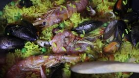 Dolly close up panning view of a Spanish seafood paella: mussels, king prawns, langoustine, haddock.  stock video footage