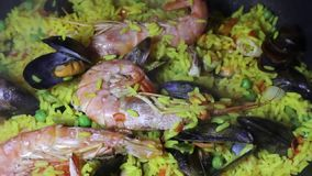 Dolly close up panning view of a Spanish seafood paella: mussels, king prawns, langoustine, haddock.  stock video