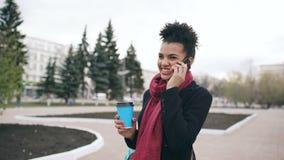 Dolly geschotene Aantrekkelijke gemengde ras het bedrijfsvrouw spreken smartphone en het drinken koffiegangen in stadsstraat met stock footage