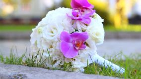 Dolly motion. Beautiful wedding bouquet of white roses and pink orchids  for bride stock video footage