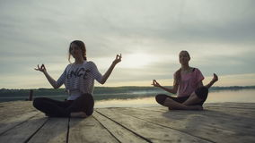 DOLLY MOTION: Two Young woman doing yoga near lake. Two Young woman doing yoga near lake outdoors, meditation. Sport fitness and exercising in nature, autumn stock video