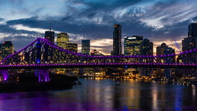 Dolly night time panorama of Brisbane city with purple lights on Story Bridge stock footage