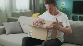 Dolly out of young man opens a cardboard parcel on the couch in his living room stock footage