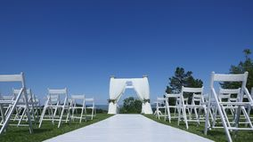 Dolly of rows of chairs at a wedding ceremony from the aisle.  stock footage