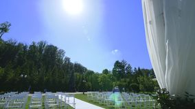 Dolly of rows of chairs at a wedding ceremony from the aisle.  stock video footage
