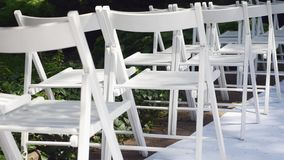 Dolly of rows of chairs at a wedding ceremony from the aisle and from the back.  stock video footage