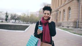 Dolly schot van aantrekkelijke gemengde ras het bedrijfsvrouw spreken smartphone en het drinken koffiegangen in stadsstraat met stock video
