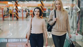 Dolly schot van mooie studentes die terwijl het lopen in winkelcomplex met document zakken in vrije tijd babbelen consumentisme stock video