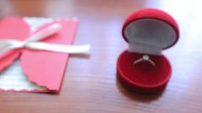 Dolly schot van trouwring in rood vakje en prentbriefkaar op de lijst stock video