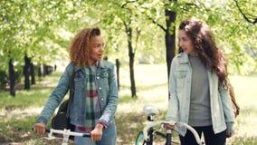 Dolly schot van vrolijke meisjesvrienden die in park met fietsen lopen na het berijden van fietsen en het socialiseren ontspannen stock videobeelden