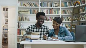 Dolly shot of african male student walking throught the library, giving five to attractive african female student and. Dolly shot of african male student walking stock footage