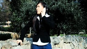Dolly shot of angry asian american woman. Business woman getting angry on the phone stock video footage