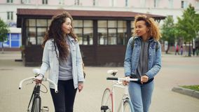 Dolly shot of attractive girls friends walking with bicycles along street with beautiful old buildings and talking stock video