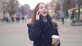 Dolly shot of attractive mixed race business woman talking smartphone and drinking coffee walks in city street stock video