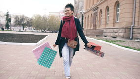 Dolly shot of Attractive mixed race girl dancing and have fun while walking down the street with bags. Happy young woman stock video