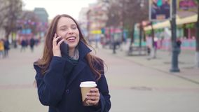 Dolly shot of attractive mixed race girl talking smartphone and drinking coffee walks in city street. Young woman stock video footage