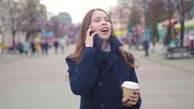 Dolly shot of Attractive mixed race girl talking smartphone and drinking coffee walks in city street. Young woman stock video