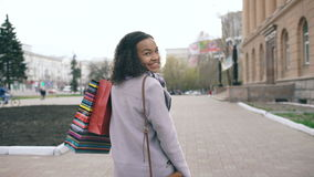 Dolly shot of Attractive mixed race girl turning around with shopping bags and smiling into camera . Young woman walking stock footage