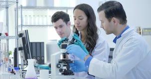 Dolly Shot av medicinsk forskningforskare Team Work på modernt laboratorium med forskare som för experiment som arbetar arkivfilmer