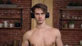 Dolly shot of beautiful fit man holding smoothies in the kitchen. Dolly shot of beautiful fit man with naked torso in head phone holding smoothies in the modern stock footage