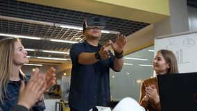 Business multi ethnic team applauding to young japanese man using virtual reality glasses for successful business. Dolly shot of business multi ethnic team stock video footage