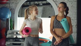 Dolly shot of cheeful young women walking together in gym and talking emotionally. Women are carrying yoga mats, bright. Dolly shot of cheeful young women stock video footage