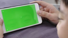 Dolly shot of child is holding a phone in his hand with a green screen for Chroma key mockup. stock video footage