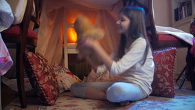Dolly shot of cute smiling girl in pajamas playing with teddy bear in house made of blankets stock footage