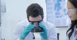 Dolly Shot dei ricercatori di ricerca medica Team Work sul laboratorio moderno con gli scienziati che eseguono gli esperimenti, l archivi video