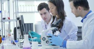 Dolly Shot dei ricercatori di ricerca medica Team Work sul laboratorio moderno con gli scienziati che eseguono gli esperimenti, l stock footage