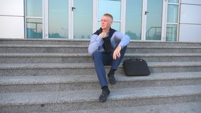 Dolly shot of desperate young businessman sitting on stairs near office building and taking off cardigan of the. Shoulders with anger outdoor. Upset sad manager stock video