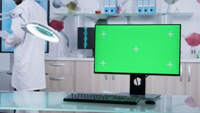 Dolly shot of doctor office with a green screen PC. On the table. In the background - modern research facility with 3D brain simulation stock footage