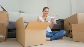 Dolly shot of happy young woman moving to a new house and using digital tablet stock video