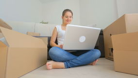 Dolly shot of happy young woman moving to a new house and using digital tablet stock footage