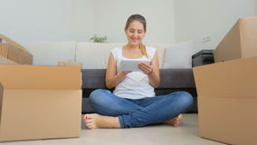 Dolly shot of happy young woman packing things in cardboard boxes and using digital tablet stock video footage