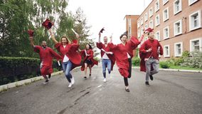 Dolly shot of joyful graduating students running with diplomas waving mortar-boards and laughing. Higher education stock video footage