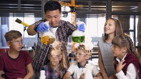 Dolly shot of Korean science man teaching young students doing chermical experiment, holding two flasks with liguid stock footage