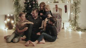 A large, close-knit family of five, father, mother, two sons and a daughter, chatting in a room at home amid Christmas. Dolly shot a large, friendly, loving stock video