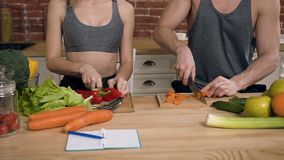 Dolly shot of male hands slicing carrot and female hands cutting pepper on wooden cutting board in the kitchen. stock video footage