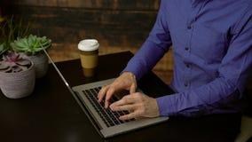 Man types on a laptop near a coffee. Dolly shot of man typing on a laptop near a coffee stock video