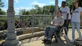 Dolly shot of a positive volunteers walking with a wheelchaired retired man stock video footage