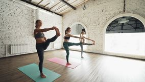 Dolly shot of pretty slim young women doing balancing yoga exercises in light loft style gym. Sports equipment, fitness stock video