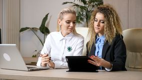 Dolly shot from right to left of two attractive businesswomen in their office working together and brainstorming new. Ideeas. Thei have a laptop and a digital stock footage